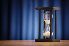 Hourglass on a dark blue background Royalty Free Stock Photos