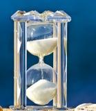 Hourglass de cristal no fundo azul imagens de stock royalty free