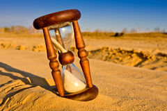 Hourglass in desert. Sandy surface Stock Photos