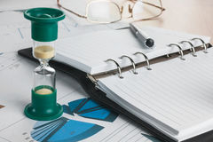 Hourglass, diary, glasses and pen Stock Photos