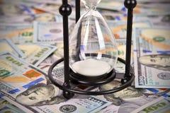Hourglass and dollar bills Stock Image