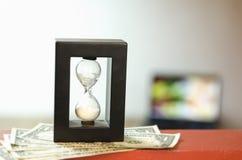 Hourglass on Dollar Bills Stock Photos