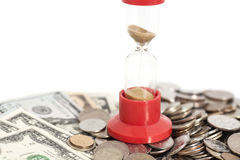 Hourglass with Dollars banknotes and coins royalty free stock image