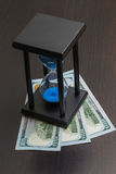 An hourglass with dollars. Royalty Free Stock Photography