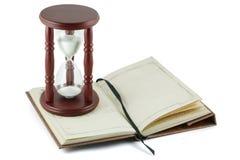 Hourglass e caderno imagem de stock
