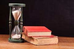 Hourglass e livros fotos de stock royalty free
