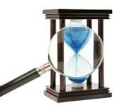 Hourglass e lupa imagem de stock