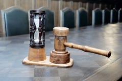 Hourglass e malho de madeira na tabela Imagens de Stock