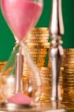 Hourglass e moedas foto de stock