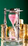 Hourglass e moedas fotografia de stock