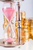Hourglass e moedas imagens de stock