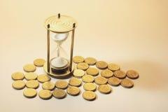 Hourglass e moedas fotos de stock royalty free