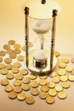Hourglass e moedas imagem de stock