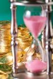 Hourglass e moedas fotografia de stock royalty free