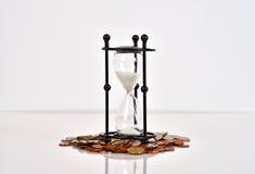 Hourglass e moedas foto de stock royalty free