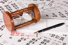 Hourglass em folhas do calendário imagem de stock royalty free