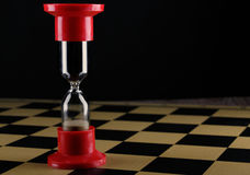 Hourglass on empty chess board, shallow DOF with selective focus stock images