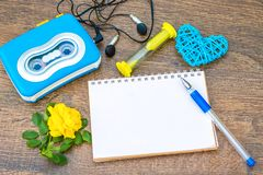 Hourglass, an empty notebook for records and audio cassette player. Time. Hourglass, an empty notebook for records and audio cassette player on the background of royalty free stock image