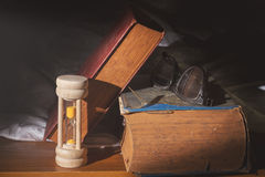 Hourglass and eyeglasses with antique books. Royalty Free Stock Photo