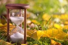 Hourglass in fallen leaves. Time is passing fast Royalty Free Stock Photo