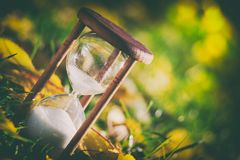 Hourglass in fallen leaves. Time is passing fast. Stock Photography