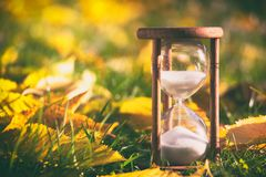 Hourglass in fallen leaves. Time is passing fast Stock Image