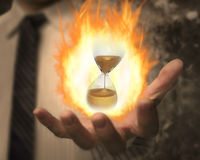 Hourglass with fire ball in business man's hand Stock Photos