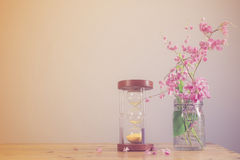 Hourglass with flowers on wood background. Royalty Free Stock Images