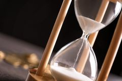 Hourglass with flowing sand on table. Time management. Hourglass with flowing sand on table, closeup. Time management Stock Photo