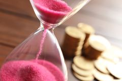 Hourglass with flowing sand on table. Time management royalty free stock photos