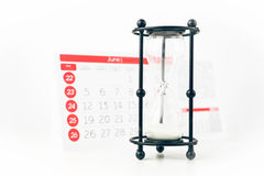 Hourglass In Front Of Calendar Closeup Royalty Free Stock Photography