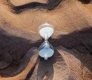 Hourglass on the frozen sand Royalty Free Stock Image