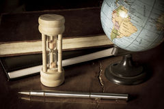 Hourglass and globe with stationary. Royalty Free Stock Images