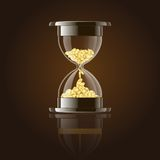 Hourglass with gold coins over dark background. Stock Photo