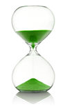 Hourglass with green sand running through Stock Images