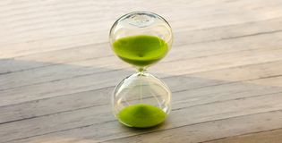 Hourglass with green sand on a wooden background royalty free stock photography