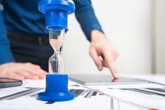 hourglass Homem de negócios que trabalha no escritório no fundo Conceito Tempo é dinheiro imagens de stock royalty free
