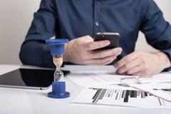hourglass Homem de negócios que trabalha no escritório no fundo Conceito Tempo é dinheiro fotografia de stock royalty free
