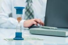 hourglass Homem de negócios que trabalha no escritório no fundo Conceito Tempo é dinheiro fotografia de stock