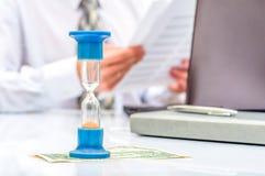 hourglass Homem de negócios que trabalha no escritório no fundo Conceito Tempo é dinheiro imagem de stock royalty free
