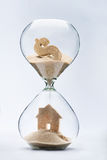 Hourglass house mortgage concept. House made out of falling sand from dollar sign flowing through hourglass Stock Images