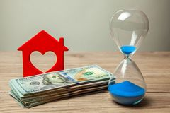 Hourglass and house symbol with money on table stock image