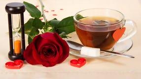 Hourglass i filiżanka herbata, różany obraz stock