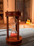 Hourglass II. Old hourglass with candles background Stock Images