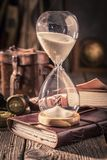 Hourglass and journal as a concept of travel memories. On old table stock photo
