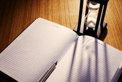 Hourglass kastingu cień na notatniku z piórem Zdjęcie Royalty Free
