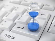 Hourglass on keyboard Stock Photos