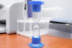 Hourglass on the laboratory table. Close-up Royalty Free Stock Photo