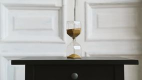 Hourglass light background, stand on a black bedside table. golden sand fray. Transparent glass hourglasses on the background of white doors stand on a dark stock video footage