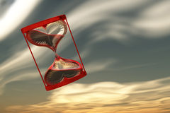 Hourglass of love. On the sky background, red clock Stock Photos
